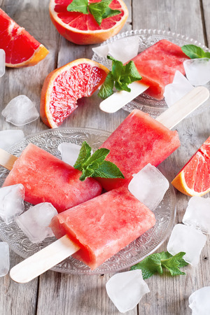 Red grapefruit homemade popsicles with ice cubes. Selective focus.