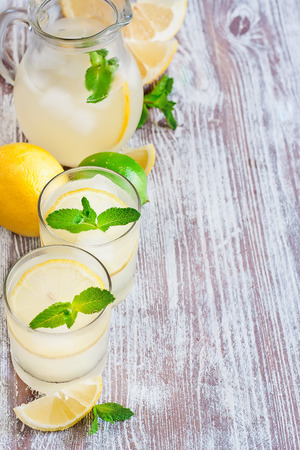 Mint lemonad in glasses and pitcher. Selective focus. Copy space background. photo