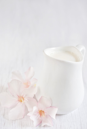 Cream in little white jug on white wooden table with rose rhododendron flowers. High key.