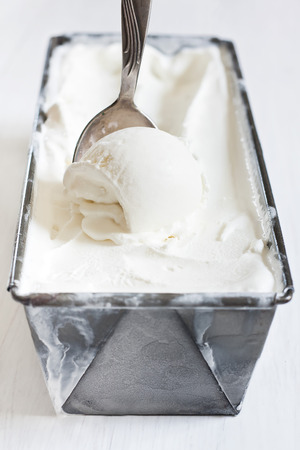 icecream: Homemade vanila ice cream in frozen metalic container. Selective focus.