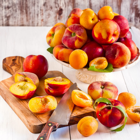Ripe apricots, nectarines and saturn peaches on ceramic holder and olive wood desk with knife.