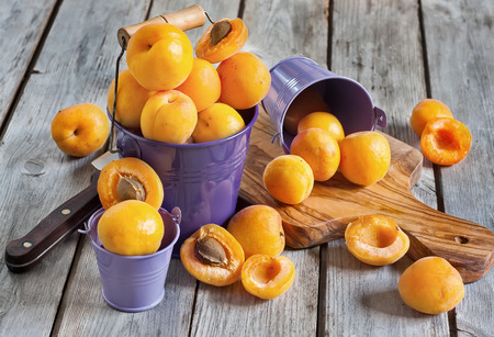 Sweet ripe apricots in small violet buckets.  photo