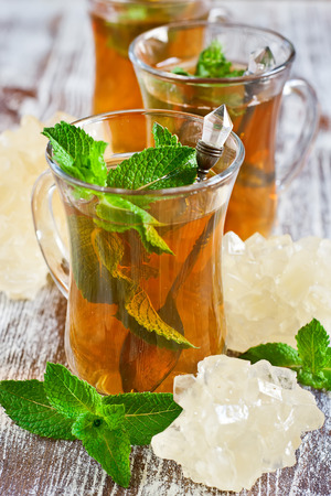 turkish dessert: Traditional turkish tea with fresh mint and light brown rock sugar or nabot.  Stock Photo