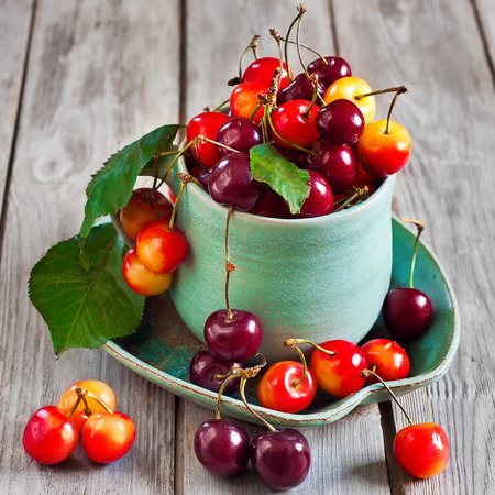 sour cherry: Ripe sweet mixed cherry in teal cup with saucer on old wooden table. Selective focus.