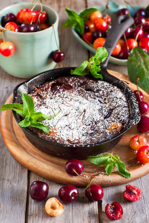 french cuisine: Chocolate clafoutis with ripe cherry on iron pan with fresh mint and sugar powder. Selective focus. Stock Photo