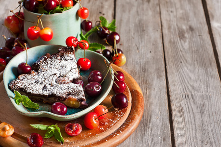 Chocolate clafoutis with ripe cherry on iron pan with fresh mint and sugar powder. Selective focus. Copy space background. Standard-Bild