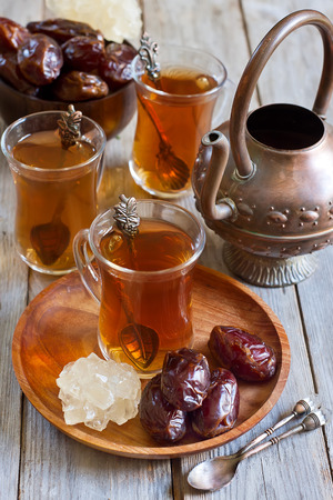 arabian food: Traditional arabic tea with dry madjool dates and rock sugar nabot. Selective focus. Stock Photo