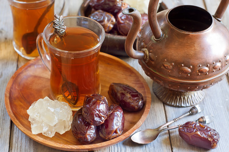 Traditional arabic tea with dry madjool dates and rock sugar nabot. Selective focus. photo