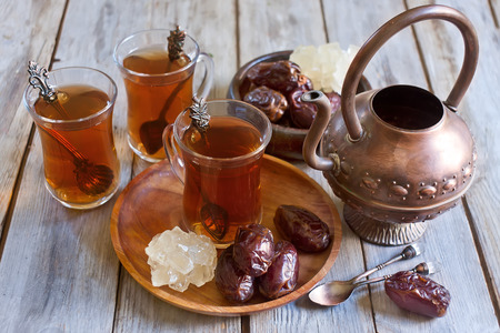 moroccan cuisine: Traditional arabic tea with dry madjool dates and rock sugar nabot. Selective focus. Stock Photo
