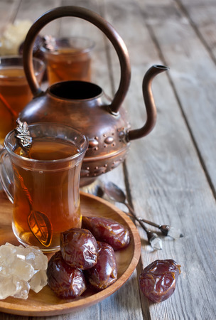 Traditional arabic tea with dry madjool dates and rock sugar nabot. Selective focus. Copy space background. Stock Photo