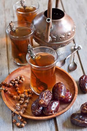 comida arabe: T� �rabe tradicional con cuentas de madera, d�tiles secos y madjool nabot az�car de la roca. Enfoque selectivo. Foto de archivo