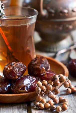 Traditional arabic tea with wood rosary and dry madjool dates . Selective focus.