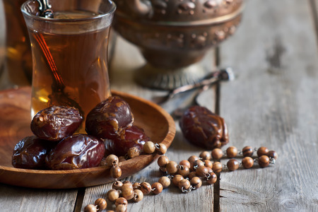 Traditional arabic tea with wooden rosary and dry madjool dates . Selective focus.