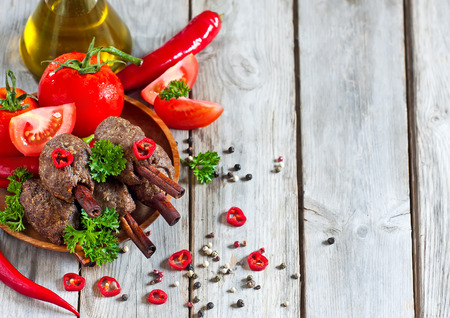 chicken kebab: Traditional lamb kebab on cinnamon sticks on wooden plate with tomato, parsley and red hot pepper