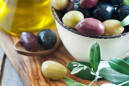 kalamata: Mixed marinated olives (green, black and purple) in ceramic bowl and wooden spoon with bottle of olive oil Stock Photo