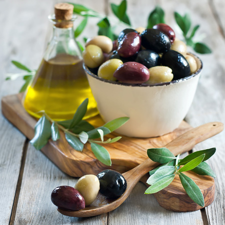 Mixed marinated olives (green, black and purple) in ceramic bowl and wooden spoon with bottle of olive oil. Selective focus.
