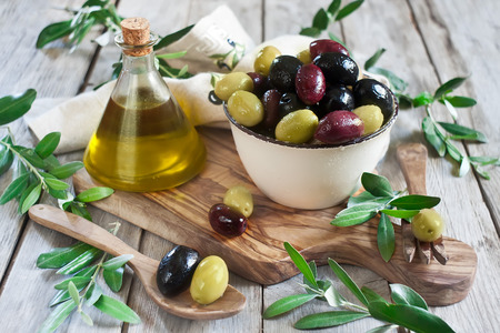 Mixed marinated olives (green, black and purple) in ceramic bowl and wooden spoon with bottle of olive oil photo