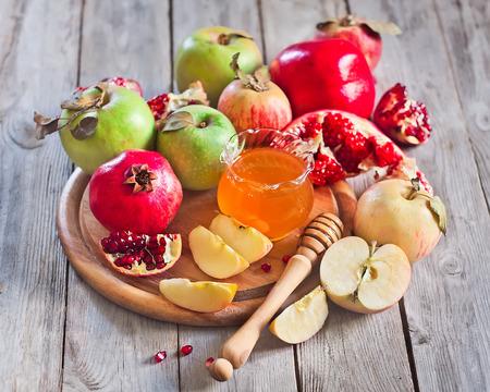 Pomegranate, apple and honey, traditional food of jewish New Year celebration, Rosh Hashana. Selective focus.
