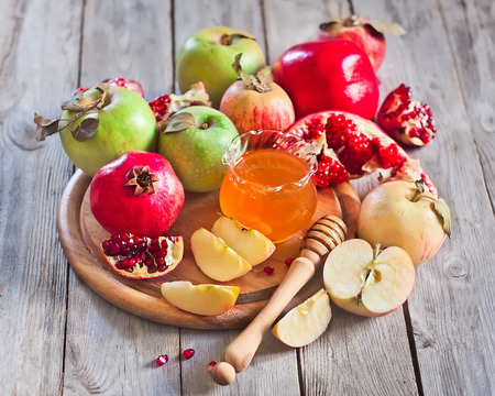 rosh hashana: Pomegranate, apple and honey, traditional food of jewish New Year celebration, Rosh Hashana. Selective focus.
