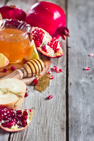Pomegranate, apple and honey, traditional food of jewish New Year celebration, Rosh Hashana. Selective focus. Copyspace background photo
