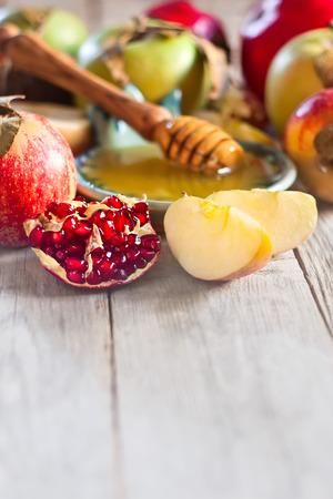 Pomegranate, apple and honey, traditional food of jewish New Year celebration, Rosh Hashana. Selective focus. Copyspace background