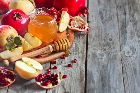 jewish new year: Pomegranate, apple and honey, traditional food of jewish New Year celebration, Rosh Hashana. Selective focus. Copyspace background