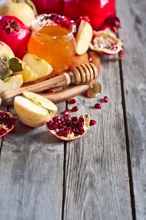 jewish food: Pomegranate, apple and honey, traditional food of jewish New Year celebration, Rosh Hashana. Selective focus. Copyspace background