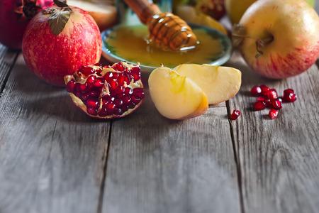 jewish cuisine: Pomegranate, apple and honey, traditional food of jewish New Year celebration, Rosh Hashana. Selective focus. Copyspace background