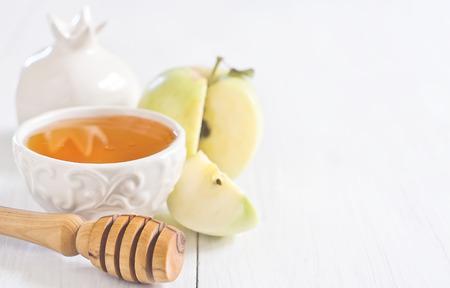 jewish cuisine: Apple and honey, traditional food of jewish New Year celebration, Rosh Hashana. Selective focus. Copyspace background. High key.