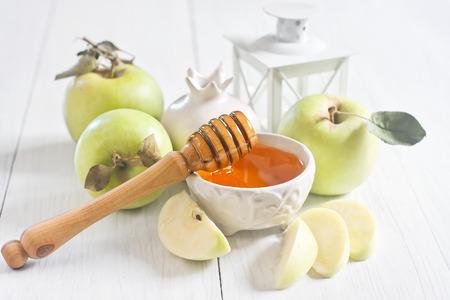 jewish cuisine: Apple and honey, traditional food of jewish New Year celebration, Rosh Hashana. Selective focus. High key.