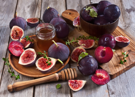 Ripe purple figs, plums, thyme and homey on olive board. Selective focus. photo