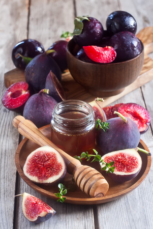 homey: Ripe purple figs, plums, thyme and homey on olive board. Selective focus.