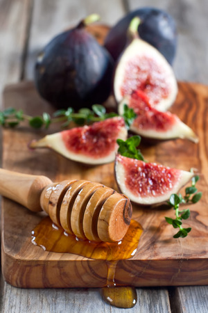 homey: Ripe purple figs, thyme and homey on olive board. Selective focus.