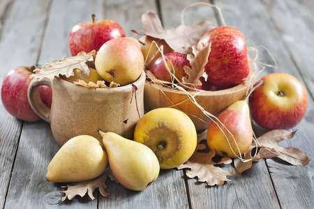 apple basket: Ripe pears and apples with dry fall leaves on wooden background. Selective focus. Stock Photo