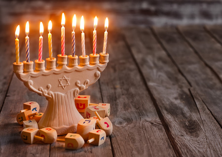 Jewish holiday hannukah symbols - menorah and wooden dreidels. Copy space bacground. photo