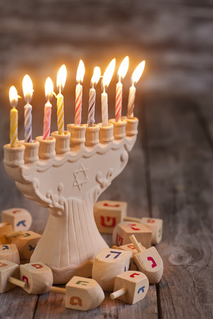 Jewish holiday hannukah symbols - menorah and wooden dreidels. Copy space bacground.