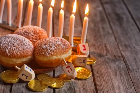 Jewish holiday hannukah symbols - menorah, doughnuts, chockolate coins and wooden dreidels. Copy space background. Standard-Bild
