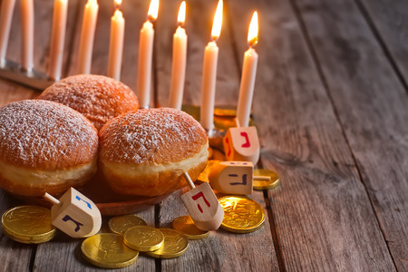 jewish food: Jewish holiday hannukah symbols - menorah, doughnuts, chockolate coins and wooden dreidels. Copy space background. Stock Photo