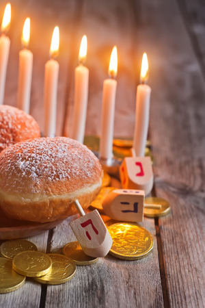 hanukka: Jewish holiday hannukah symbols - menorah, doughnuts, chockolate coins and wooden dreidels. Copy space background. Stock Photo