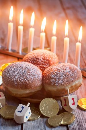 dreidels: Jewish holiday hannukah symbols - menorah, doughnuts, chockolate coins and wooden dreidels. Stock Photo
