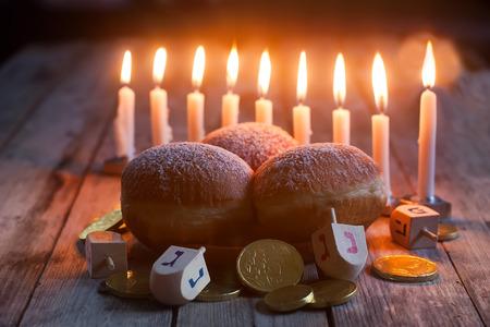 Jewish holiday hannukah symbols - menorah, doughnuts, chockolate coins and wooden dreidels. Standard-Bild