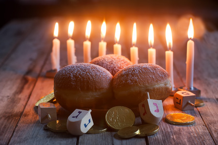 Jewish holiday hannukah symbols - menorah, doughnuts, chockolate coins and wooden dreidels. Stock Photo