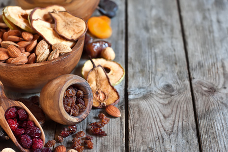 dry food: Mix of dried fruits and almonds - symbols of judaic holiday Tu Bishvat. Copyspace background. Stock Photo