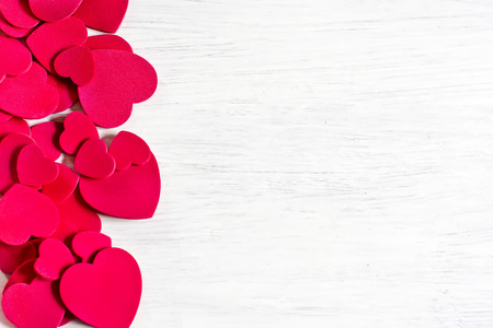 Various size valentines day hearts on white wooden background. Copy space background. photo