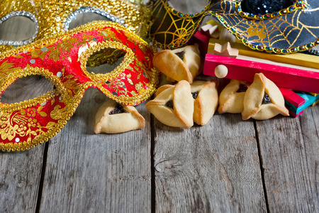 Hamantaschen cookies or Hamans ears, noisemaker and carnival masks for Purim celebration (jewish holiday). Copy space background. Stock Photo