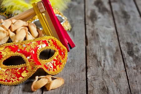 hamantasch: Hamantaschen cookies or Hamans ears, noisemaker and carnival masks for Purim celebration (jewish holiday). Copy space background. Stock Photo
