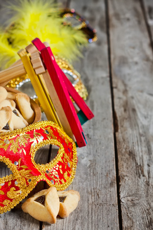 noisemaker: Hamantaschen cookies or Hamans ears, noisemaker and carnival masks for Purim celebration (jewish holiday). Stock Photo
