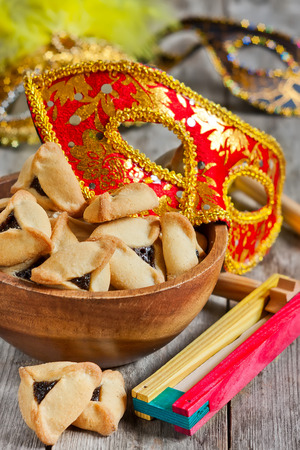 megillah: Hamantaschen cookies or Hamans ears, noisemaker and carnival masks for Purim celebration (jewish holiday). Stock Photo
