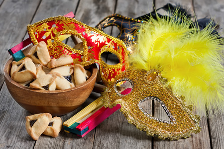 Hamantaschen cookies or Hamans ears, noisemaker and carnival masks for Purim celebration (jewish holiday). Stock Photo