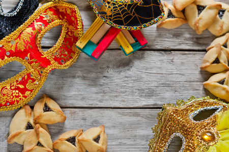 purim: Hamantaschen cookies or Hamans ears, noisemaker and carnival masks for Purim celebration (jewish holiday). Copy space background. Stock Photo